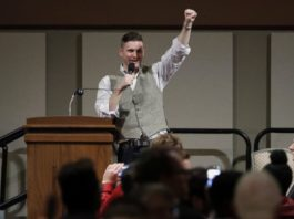 Richard Spencer gives white power salute during a talk at Texas A&M University, Dec 2016 (source: AP via ABC news, https://abcnews.go.com/US/hundreds-protest-white-nationalist-texas-university/story?id=44029112)